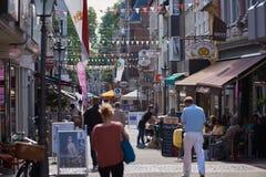 NEUSS, GERMANIA - 8 AGOSTO 2016: Pedestrants che cammina lungo una strada dei negozi della città immagini stock libere da diritti