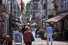 NEUSS, GERMANY - AUGUST 08, 2016: Pedestrants walking along a city shopping street. With bars royalty free stock images