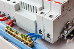 Neutral bus connected by blue wires closeup against automatic circuit breakers in the white plastic mounting box royalty free stock images
