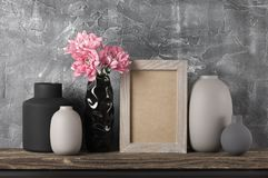 Neutral colored home decor. Pink flowers in neutral colored vases and frame on distressed wooden shelf against rough plaster grey wall. Home decor royalty free stock photography
