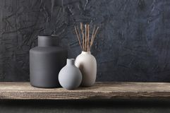Neutral colored home decor. Neutral colored vases with wood sticks on distressed wooden shelf against rough plaster black wall. Home decor stock photo