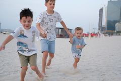 Three brothers are running on the beach, holding hands royalty free stock images