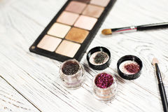 Neutral eye shadows, pigments, glitter, brushes and eyeliner Stock Photography