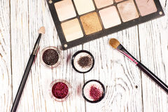 Neutral eye shadows, pigments, glitter, brushes and eyeliner. Collection of cosmetics for make-up artist. Neutral eye shadows, pigments, glitter, brushes and Royalty Free Stock Photography