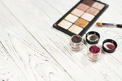 Neutral eye shadows, pigments, glitter, brushes and eyeliner. Collection of cosmetics for make-up artist. Neutral eye shadows, pigments, glitter, brushes and Stock Image