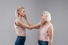 Neutral young blonde girl caressing cheek of her senior mother royalty free stock photo