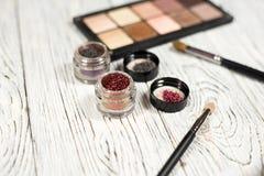 Neutrala ögonskuggor, pigment, blänker, borstar och eyeliner Arkivbild