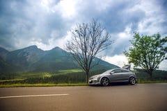 Neuwagenauf eine Straße in den Bergen schnell fahren Lizenzfreies Stockfoto