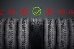 Neuwagenreifen mit dem grünen Häkchen, das heraus unter alten Reifen steht Lizenzfreie Stockfotografie