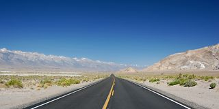 Nevada highway. Panorama of highway in nevada desert, road with yellow line in the middle and mountains around, the clear sky can be used as background Royalty Free Stock Photos