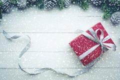 Nevadas en la caja de regalo roja de los regalos de Navidad con el elemento del pino de la frontera Fotos de archivo