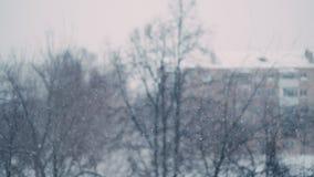 Nevadas pesadas en la ciudad Tiroteo de la ventana con el efecto del bokeh metrajes