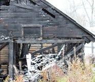 Nevado abandonó la casa negra de madera del fuego quemado Imágenes de archivo libres de regalías