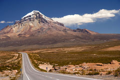 Majestic Nevado Sajama volcano. Beautiful road at the foot of the Nevado Sajama volcano in the National Park in Bolivia stock photos