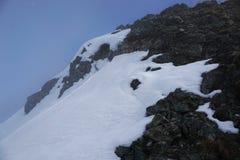 Neve bianca e grandi pietre in montagna del Cervino in svizzero Immagine Stock