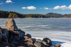 Neve branca congelada no gelo, nuvens brancas da água do lago da formação de rocha Bulgária, montanhas de Rhodopes, lago Shiroka  imagens de stock