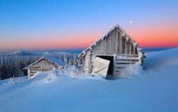 A neve branca incandesce a cor do céu O suporte velho das cabanas nos vales Dia de inverno frio imagens de stock