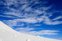 Neve, céu e nuvens nas montanhas Fotografia de Stock Royalty Free