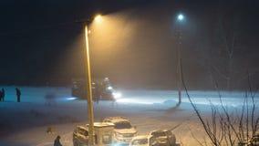 A neve cai na rua na perspectiva de um poste de luz na noite Lapso de tempo filme