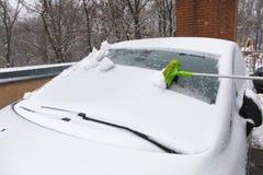 Neve che spazzola con una spazzola lunga dal parabrezza della vostra automobile fotografie stock libere da diritti