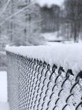 A neve cobriu a cerca com fundo nevado fotografia de stock royalty free
