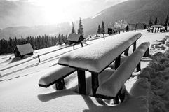 A neve cobriu a tabela e os bancos nas montanhas Fotografia de Stock