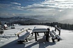 A neve cobriu a tabela e os bancos nas montanhas Imagem de Stock