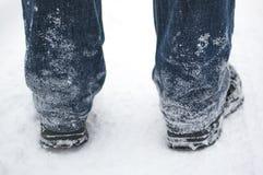 Neve congelada em calças de brim e em botas pretas de um homem no inverno, vista traseira fotografia de stock