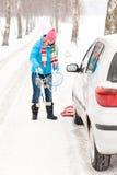Neve da mulher que está com as correntes de pneu do carro Foto de Stock Royalty Free