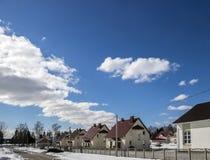 A neve da rua do dia ensolarado encontra-se com o fundo das nuvens do céu azul da estrada dos custos do carro das casas de campo  Imagem de Stock