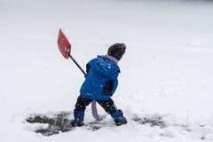Neve de ajuda da pá do menino novo em um blizzard foto de stock