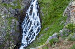 A neve de derretimento cria um waterfal em montanhas rochosas Imagens de Stock