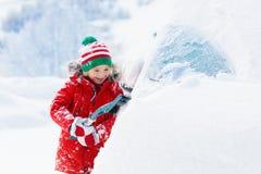 Neve de escovadela da criança fora do carro após a tempestade Criança com escova do inverno e carro de família do esclarecimento  fotos de stock royalty free