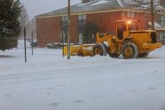 Neve de limpeza do trator na rua e um parque de estacionamento após a queda de neve imagens de stock