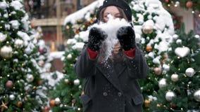 Neve de sopro da menina do inverno da beleza no centro da cidade outdoors Flocos de neve do voo Jovem mulher alegre que tem o div vídeos de arquivo