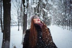 Neve de sopro da menina do inverno da beleza no parque gelado do inverno fotografia de stock royalty free