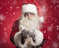 A neve de sopro de Papai Noel lasca-se fora de suas mãos fotos de stock royalty free
