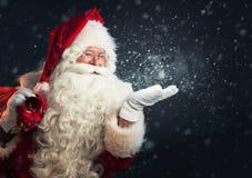 Neve de sopro de Santa Claus de suas mãos fotos de stock