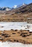 Neve del witn delle montagne e sotto con i turisti sulla terra con erba marrone, neve e lo stagno congelato nell'inverno ad allo  Fotografia Stock Libera da Diritti
