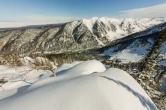 A neve deriva na inclinação da montanha no por do sol, negligenciando o vale da montanha Fotografia de Stock