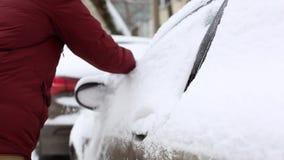 Neve di pulizia dell'uomo dall'automobile a mano nel distretto vivente della casa archivi video