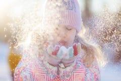 Neve di salto dalle mani, inverno della bambina Fotografia Stock