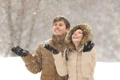 Neve di sorveglianza delle coppie divertenti nell'inverno Immagine Stock