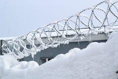 Neve e filo spinato sul recinto vicino alla costruzione immagini stock libere da diritti