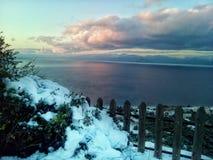Neve e mare sotto le nuvole grige fotografia stock libera da diritti
