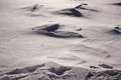A neve e o vento combinaram ondas formadas da neve em um ambiente agrícola fotos de stock