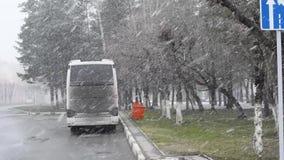 Neve e vento nel pomeriggio della citt? in primavera sui precedenti delle case e dei segnali stradali archivi video