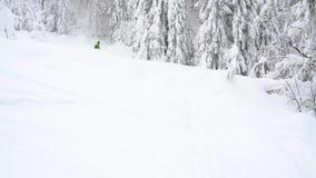 Neve fresca do pó da equitação extrema do snowboarder abaixo da inclinação de montanha íngreme vídeos de arquivo