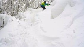 Neve fresca do pó da equitação extrema do snowboarder abaixo da inclinação de montanha íngreme Movimento lento video estoque