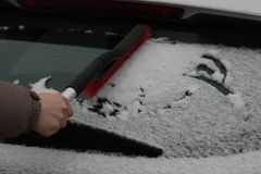 Neve leggera su vetro Fiocco di neve sulla finestra di automobile Sensibilità dell'inverno e delle feste Fondo Liberi l'automobil fotografia stock libera da diritti
